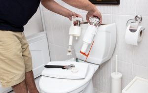 a man fixing the toilet tank
