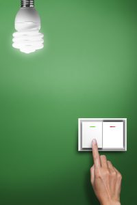Hand press on a green wall light switch
