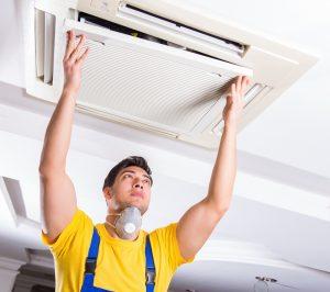 Repairman concealing home HVAC unit