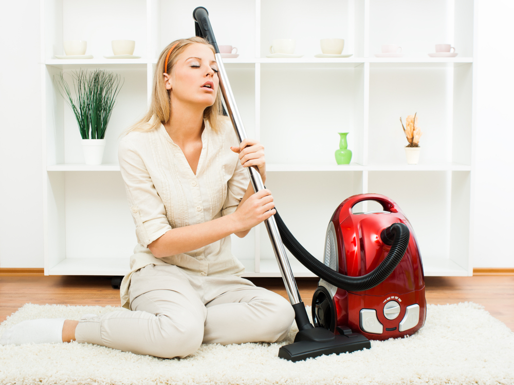 exhausted woman with a vacuum cleaner